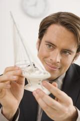 Geschäftsmann hält ein Modell eines Schiffes, Portrait