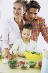 Eltern beobachten Tochter die Salat macht