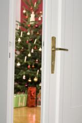 Blick durch offene Tür auf Weihnachtsbaum und Geschenke