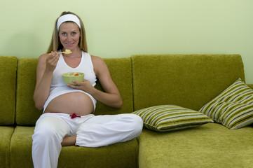 Schwangere Frau auf dem Sofa, mit Früchten