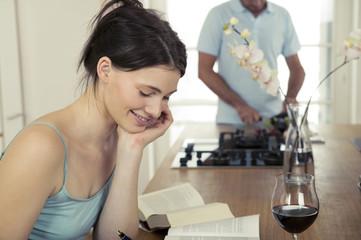 Junge Frau arbeitet in der Küche, Mann Kochen