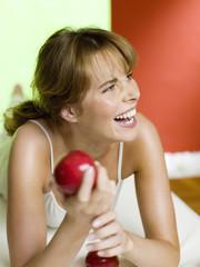 Frau liegt auf dem Bett und hält Apfel, lachen, Nahaufnahme