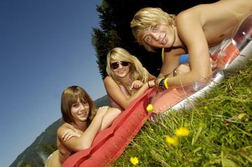 Drei junge Erwachsene, die auf Luft-Bett, lächelnd, Porträt-, Neige-Ansicht