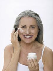 Ältere Frau benutzt Gesichtscreme, Portrait