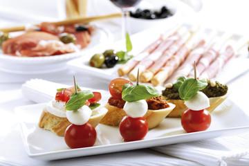 Grissini mit Parmaschinken und Oliven und Mozzarella mit Tomaten, italienische Vorspeisen