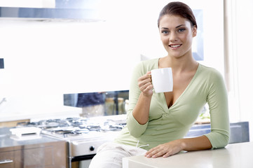 Junge Frau in der Küche, hält Tasse