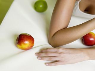 Frau liegt auf dem Bett mit Äpfeln