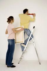 Junges Paar hängt Gemälde auf, Mann auf Leiter