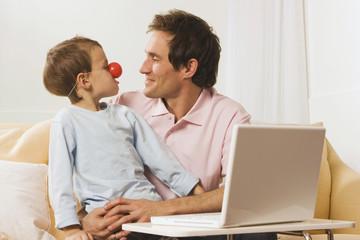 Vater und Sohn am Laptop, Junge trägt Clown-Nase