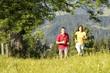 Junges Paar joggend auf Wiese, Berge im Hintergrund