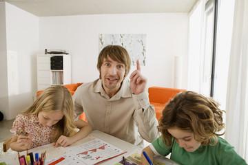 Vater und Kinder bei den Hausaufgaben