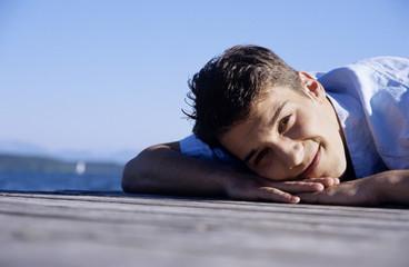 Junger Mann auf Steg, lächelnd, Nahaufnahme