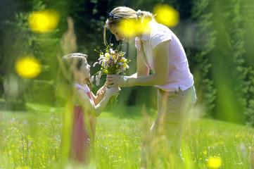 Mutter gibt Blumenstrauß an Tochter auf Wiese, Seitenansicht