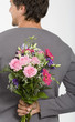 Junger Mann mit Blumenstrauß hinter dem Rücken, lächelnd, Nahaufnahme