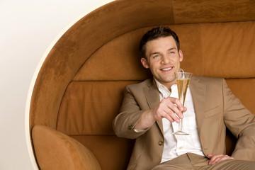 Mann sitzt auf dem Sofa und hält Glas Champagner, lächelnd