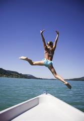 Teenager, Mädchen springt vom Boot ins Wasser, Rückansicht