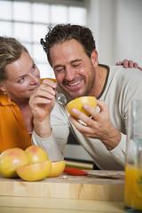 Älteres Paar Grapefruit essend in der Küche, Lächeln, Nahaufnahme