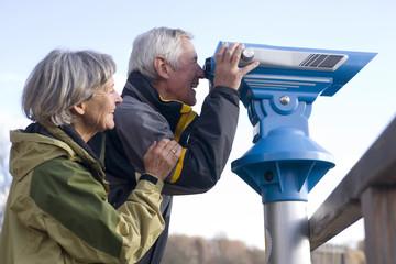 Älteres Paar, Mann schaut durch Teleskop, Seitenansicht