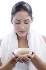 Junge Frau hält Teeschale, die Augen geschlossen, Nahaufnahme