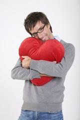Junger Mann hält herzförmiges Kissen, Lächeln, Portrait