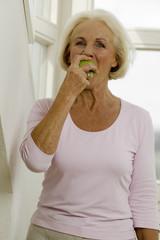 Ältere Frau isst Obst, Portrait