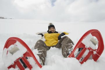 Italien, Südtirol, junge Frau mit Schneeschuhen, im Schnee liegend