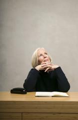 Seniorin sitzt am Tisch mit Buch, aufblicken