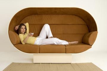 Junge Frau auf Sofa liegend mit Fernbedienung