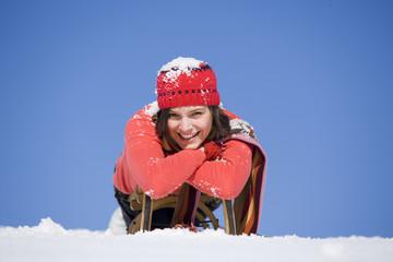Frau mit Schnee bedeckt liegt auf Schlitten, lächelnd
