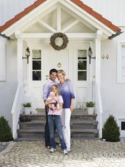 Familie mit Baby stehend vor Eigenheim
