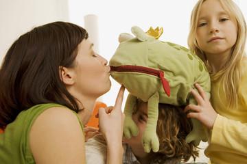 Mutter mit Kindern spielend, sie küssen einen Spielzeugfrosch