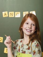 Mädchen vor der Tafel, mit Bleistift, Schule