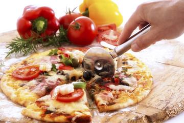 Mann schneidet Pizza mit Radschneider