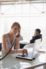 Geschäftsfrau mit Laptop während des Telefonierens, männliche Kollegen im Hintergrund