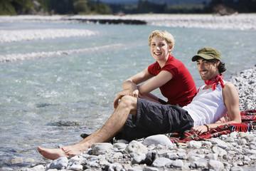 Deutschland, Bayern, Tölzer Land, Junges Paar sitzt am Flussufer