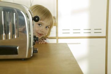Mädchen hinter Toaster in der Küche, Nahaufnahme, Portrait