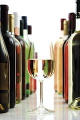 Glas Weißwein zwischen Weinflaschen, Nahaufnahme