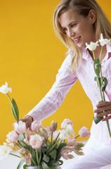 Junge Frau arrangiert Blumen in der Vase