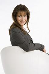 Geschäftsfrau sitzt auf dem Stuhl, lächelnd, Porträt