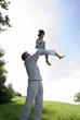 Vater hebt Sohn im Park, Seitenansicht