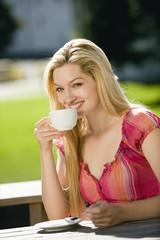 Deutschland, Bayern, Oberbayern, junge Frau mit einer Tasse Kaffee in Biergarten, Portrait