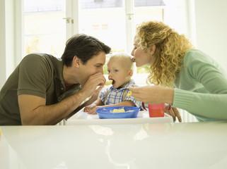 Junge Familie, Vater füttert Baby