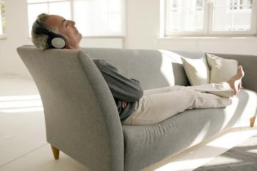 Mann mit Kopfhörern, sitzt auf dem Sofa, die Augen geschlossen