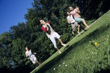 Vier junge Leute, die durch den Garten laufen