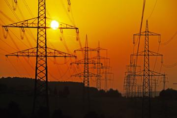 Strommasten und Stromleitungen bei Sonnenuntergang