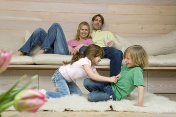 Junge und Mädchen kämpfen auf dem Teppich, die Eltern im Hintergrund, Portrait
