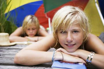 Teenager, Mädchen liegen unter Sonnenschirm am Bootssteg, Buch lesend, Nahaufnahme
