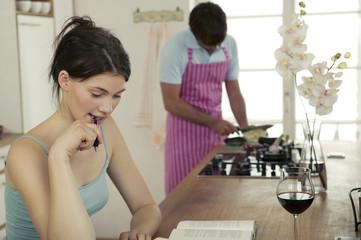 Frau arbeitet in der Küche, Mann Kochen