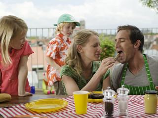 Familie essend auf dem Balkon