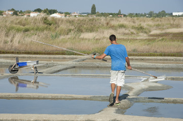 Salt pans France worker skimming salt